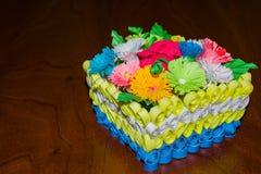 Korb mit bunten Papierblumen in der Technik von Rüschen Stockbild