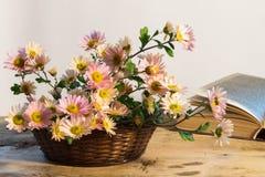Korb mit empfindlichem Blumenstrauß von Chrysanthemen auf einem Hintergrund O Stockbild