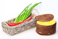 Korb mit grünen Zwiebeln und roten Pfeffern Lizenzfreie Stockfotos