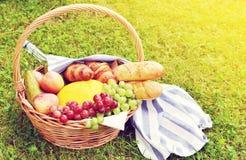 Korb mit Lebensmittel-Frucht-Bäckerei-Käse Ham Tomato Picnic Green Grass tonte Foto Stockbilder