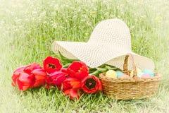 Korb mit Ostereiern, rote Tulpen, Hut Lizenzfreies Stockfoto