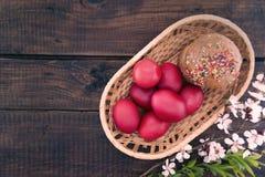 Korb mit Ostern-Kuchen und roten Eiern auf rustikalem Holztisch oberseite Lizenzfreie Stockfotos