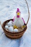Korb mit Utensilien auf Ostern, Hahn und Ostereiern, die im Korb im Schnee liegen Stockfotografie