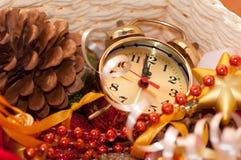 Korb mit Weihnachtsspielwaren und den Uhrhänden Lizenzfreie Stockfotos