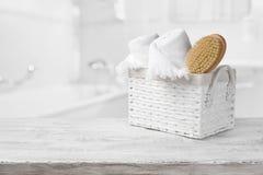 Korb, Tücher und Badebürste auf Holz über unscharfem Badezimmer stockfotografie