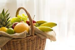 Korb voll von Früchten auf einem hellen Hintergrund - hoher Schlüssel Stockfotografie