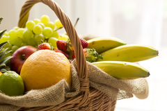 Korb voll von Früchten auf einem hellen Hintergrund - hoher Schlüssel Stockbild