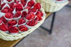 Korb voll von Kornetten füllte mit Rotrose für die Heirat stockfoto