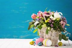 Korb von Blumen und von Ostereiern auf einem hölzernen Hintergrund Lizenzfreie Stockfotos