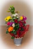 Korb von bunten Blumen auf einem Bretterboden Stockfotos