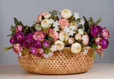 Korbgrauhintergrund der künstlichen Blumen Stockbild
