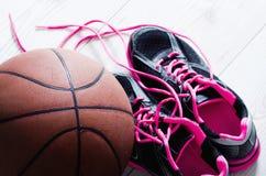 Korbturnschuhe und -ball Stockfoto