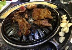 Koreański grill, mięso, pieczarki, czosnek, rozdrapani jajka przygotowywa na metalu dysku na ogieniu od benzynowego palnika obraz stock