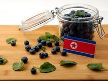 Koreańczyk Z Korei Północnej flaga na drewnianej desce z czarnymi jagodami dalej Obrazy Stock