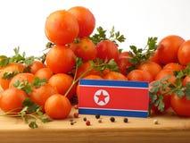Koreańczyk Z Korei Północnej flaga na drewnianym panelu z pomidorami odizolowywającymi na a Zdjęcia Stock