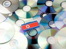 Koreańczyk Z Korei Północnej flaga na górze cd i DVD stosu odizolowywającego na bielu Fotografia Royalty Free