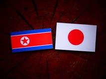 Koreańczyk Z Korei Północnej flaga z japończyk flaga na drzewnym fiszorku odizolowywającym Obrazy Royalty Free