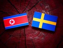 Koreańczyk Z Korei Północnej flaga z szwedami zaznacza na drzewnym fiszorku Obrazy Stock