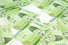 10000 Korea segrade räkningar på tabellen som pengarbakgrund Sydkorean Arkivbild