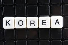 Korea teksta słowa tytułowego podpisu etykietki pokrywy tła tło Abecadło listu zabawki bloki na czarnym odbijającym tle Biały al Zdjęcia Stock