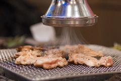 A closeup of a Korean BBQ exhaust fan sucking smoke from the BBQ stove. stock images