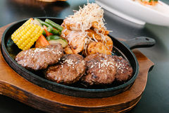 Korean bbq sizzle plate with other dishes in the background. Korean bbq with meat, corn and potatoes stock image