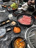 Korean bbq table spread. Korean bbq meat plate brisket hot raw beef table spread soup kimchi radish garnish side appetizers food dining restaurant royalty free stock photo