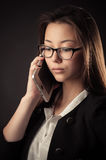 Korean beautiful teenage girl talking on mobile phone. Isolated on black background Stock Images