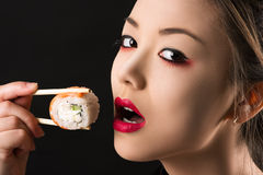 Korean beautiful teenager girl with bright makeup eating a roll. Isolated on black background Stock Photos