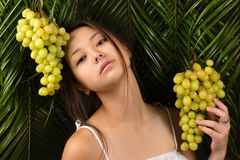 Korean beautiful teenager girl with green grapes. In studio Stock Photo