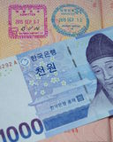 A Korean bill of 1,000 won rests on a russian passport with entry and exit stamps Stock Photo