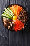 Korean cuisine: Bibimbap with beef, raw yolk, vegetables and ric. E macro on a plate. Vertical top view from above Royalty Free Stock Photography
