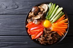 Korean cuisine: Bibimbap with beef, raw yolk, vegetables and ric. E on a plate. horizontal top view from above Royalty Free Stock Photos