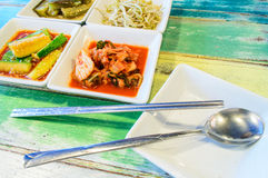 Kimchi on white square dish with spoon and Chops Royalty Free Stock Photography