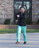 Korean doctor running down her driveway Royalty Free Stock Images