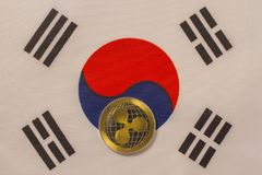 Korean flag with bitcoin, physical metal coin. Physical, metal cryptocurrency coin on textile Korean flag stock photography
