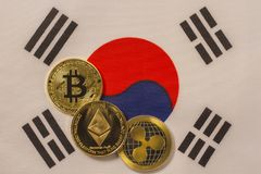 Korean flag with bitcoin, physical metal coin. Physical, metal cryptocurrency coin on textile Korean flag royalty free stock images