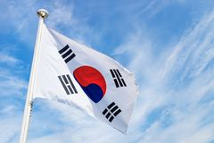 Korean flag with wind on blue sky. With light white clouds royalty free stock image
