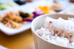 Korean food. A bowl of white rice in the foreground with plates of banchan out of focus behind stock photos