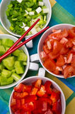 Korean food bowls with vegetables. Table setting for Korean food party with white ceramic bowls with colorful vegetables cut into small pieces ready to be taken Stock Photos