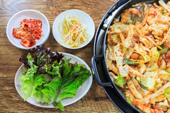 Korean food. Compose of kimchi,fresh lettuce, bean sprouts and stir-fried vegetables with chicken on wood table Stock Image