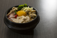 Korean Food. A heated stone bowl dish of korean food with raw eggs and seafood Royalty Free Stock Photography