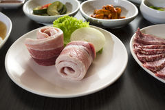 Korean Food. A horizontal shot of sliced pork belly with korean side dishes Royalty Free Stock Photography