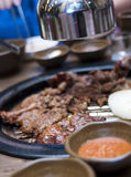 Korean food in restaurant. Typical South Korean food table setting in a restaurant. Meat being roasted on the grill in the middle of table Royalty Free Stock Image