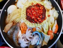 Korean food style,  Selective focus of Instant noodles with vegetable, pork sliced, mussel, squid and shrimp in hot pot on wooden stock photography