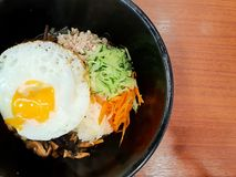 Korean food style, Top view of Rice is topped with seasoned vegetables, meat and side up fried egg on top in a black bowl. stock photo