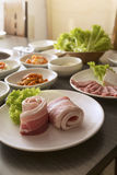 Korean Food. A vertical shot of sliced pork belly with korean side dishes Stock Photo