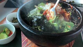 Korean hot stone dish. Stirring a Korean hot stone bibimbap in Kobe city, Japan stock footage