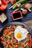 Korean japchae or chapchae, vertical, top view. Korean japchae or chapchae sweet potato starch noodles, dangmyeon, beef and various vegetables, shiitake stock photos