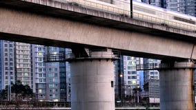 Korean KTX train crossing bridge. Korean KTX high speed train crossing bridge with apartments and city lights in the background stock footage
